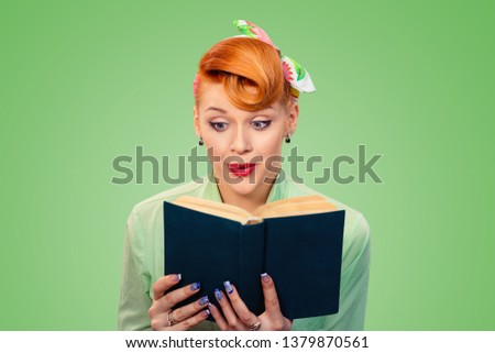 Shocking lines. Shocked amazed, surprised beautiful pinup retro hair style girl reading a book with eyes wide open isolated green background with copy space. Positive emotion face expression