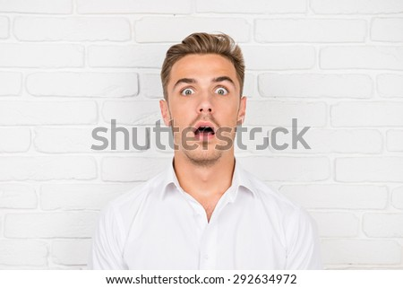 Shocking news. Surprised young man in shirt  Stock photo ©