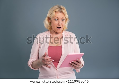 Shocking news. Upbeat middle-aged woman looking stunned after reading a message from her pink tablet