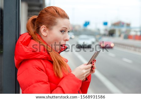 Shocking SMS. Closeup portrait funny shocked scared young girl looking at phone receiving bad news photos message with stunned emotion on face on a bus station near a road. Model in red winter coat