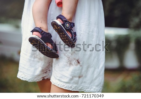 shod feet of a child in the arms of a mother, a white dress, stained with shoes, raising children and loving them
