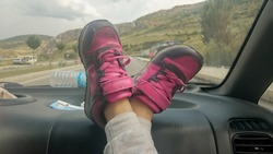 Shoe of a little girl and extending the legs her legs in the car while moving on the road