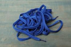 Shoelaces on light blue wooden background. Stylish accessory