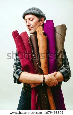 Shoemaker holds set of color leather in his workshop. Craftsman standing in his workshop. Confident man has idea for new leather products. Skilled leather manufacture worker with rolls of leather.