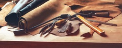 Shoemaker's work desk. Tools and leather at cobbler workplace. Set of leather craft tools on wooden background. Shoes maker tools on wooden table