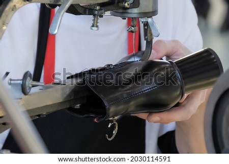 Shoemaker, shoes master using sewing machine and repairing black leather women footwear at workshop - close up Foto stock ©