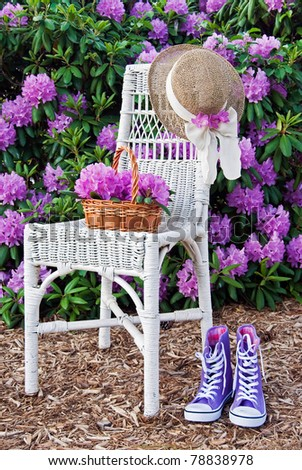 shoes and hat with wicker chair in summer garden - stock photo