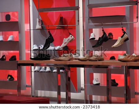 Shoes and sneakers in illuminated shelf - stock photo