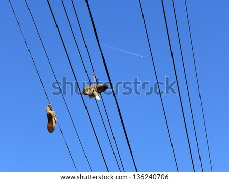 Shoes hanging from power lines contrasted with a jet airliner high overhead
