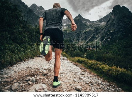 Shoes of trail runner, mountains in background - trail running concept sport photo, edit space #1145989517