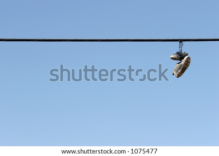 shoes on power lines - urban scene, worn tennis shoes hanging from a power line against clear blue sky. plenty of copyspace.
