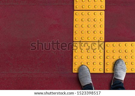 shoes on rough yellow dot tactile paving for blind handicap on tiles pathway in japan, walkway for blindness people. #1523398517