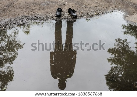 Shoes with shadow without the human / Reflection of shadow. Invisible man. Reflection of a man in a puddle. Photo stock ©
