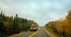 Shool bus on country road in autumn