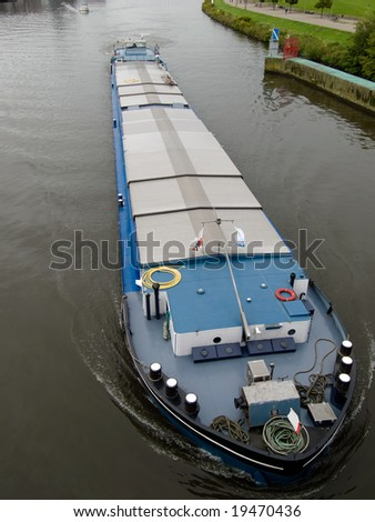 Shoot of big barge on Maas river from bridge in Netherlands.