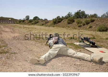 Shooter on the ground taking a shot at a distant target