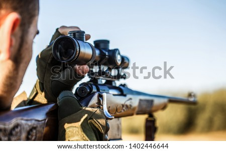Shooter sighting in the target. The man is on the hunt. Hunt hunting rifle. Hunter man. Hunting period. Male with a gun. Close up. Hunter with hunting gun and hunting form to hunt. Hunter is aiming.
