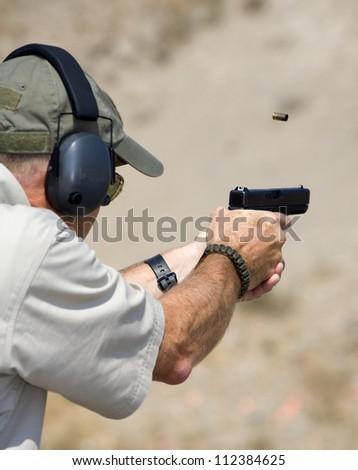 Shooter with a polymer handgun who has just taken a shot