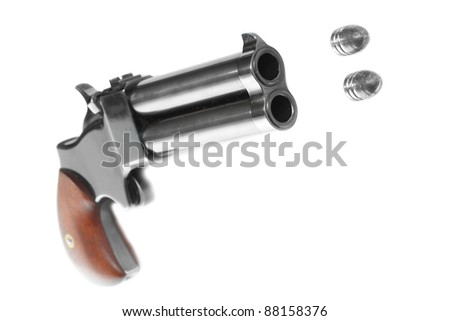 Shooting hand gun (2 shot .45 cal derringer) with two flying bullets. Close up with shallow DOF. - stock photo