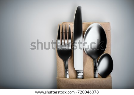 Shooting in the Studio .Fork,spoon,knife and small spoon wrapped in light brown cloth ,light background, etc.The view from the top.