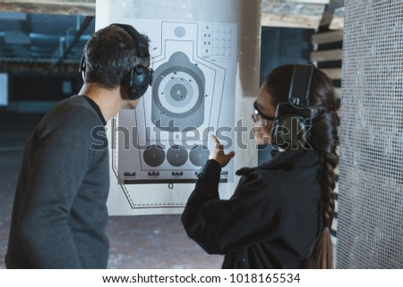 shooting instructor pointing on used target in shooting range #1018165534