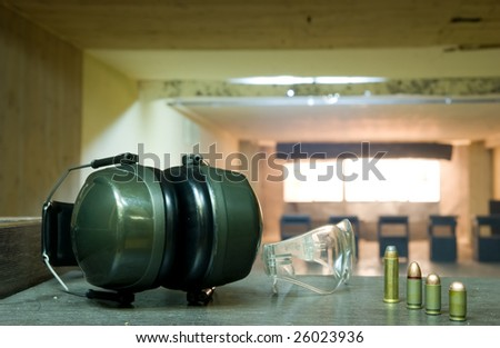 shooting range composition with cartriges, google and headset, close up - stock photo