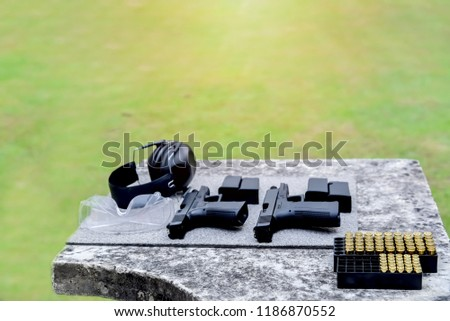 Shooting range. Gun, bullets, ear plugs and shooting accessories on the table at shooting range.