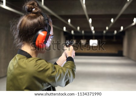 Shooting range. Shooting with a gun. Measuring to a paper target on the shooting range.  #1134371990