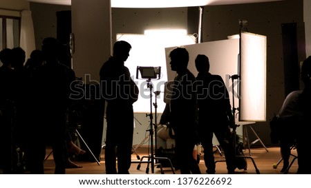Shooting studio behind the scenes in silhouette images which film crew team working for filming movie or video with professional lighting and equipment such as camera, tripod, soft box, monitor #1376226692