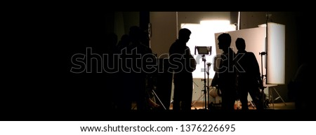 Shooting studio behind the scenes in silhouette images which film crew team working for filming movie or video with professional lighting and equipment such as camera, tripod, soft box, monitor #1376226695