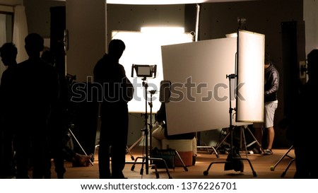 Shooting studio behind the scenes in silhouette images which film crew team working for filming movie or video with professional lighting and equipment such as camera, tripod, soft box, monitor #1376226701