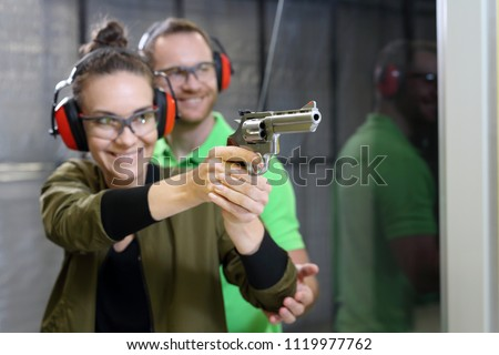 Shooting training.  The woman shoots from the gun at the shooting range under the supervision of an instructor.