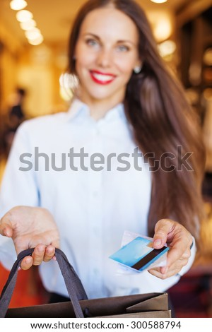 Shop assistant handing a card to a customer (soft focus on a card)