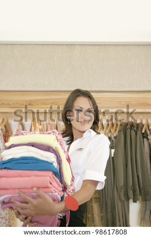 Shop assistant holding a pile of clothes in a fashion store