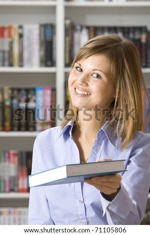 Shop assistant offering book in the bookshop