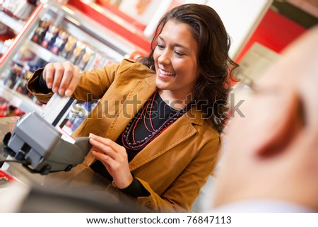 Shop assistant smiling while swiping credit card in supermarket with customer in the foreground