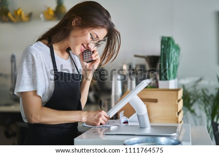 shop assistant taking order on phone in restaurant