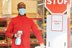 Shop employee at the entrance of the supermarket spraying disinfectant on customers hands for safety measures during covid-19