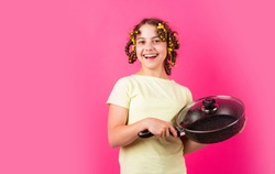 Shop home utensils. Kitchen accessories. Culinary and house duties. Stereotype housewife style. Small girl with curlers in hair. Girl hold Frying Pan. Little kid hold pan cooking meal. Pin up style.