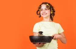 Shop home utensils. Kitchen accessories. Culinary and house duties. Stereotype housewife style. Small girl with curlers in hair. Pin up style. Girl hold Frying Pan. Little kid hold pan cooking meal.