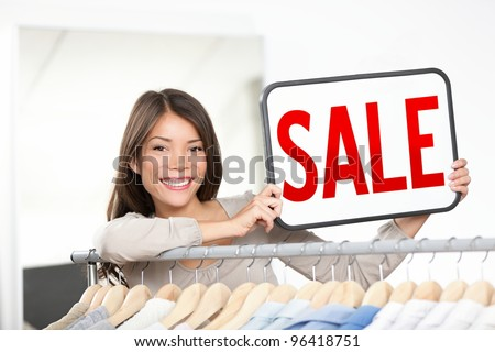 Shop owner woman sale sign. Retail store owner showing sale sign smiling happy behind clothing rack. Young female professional entrepreneur in small shop. Mixed race Chinese Asian / Caucasian woman