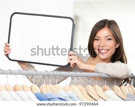 Shop sign woman. Small retail business owner showing blank sign in clothing store. For shopping or sale. Beautiful mixed race Caucasian / Chinese Asian woman in her twenties standing by clothes rack.