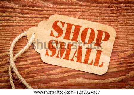 Shop Small - Small Business Saturday concept - a paper price tag with a twine against burlap canvas #1235924389