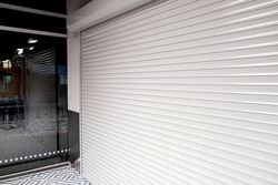 Shop window with roller shutters for protection from vandals.