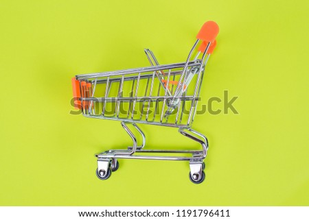 Shopaholic shopper ad concept. Close up top above overhead high angle close up view photo of one single shine tiny toy pushcart isolated on juicy saturated green color background copy space #1191796411