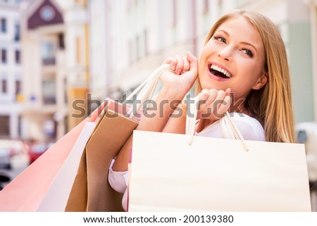 Shopaholic woman. Beautiful young cheerful woman holding shopping bags and expressing positivity while standing outdoors
