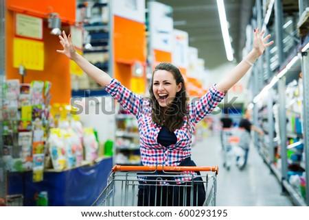 Shopaholic woman enjoying shopping spree in supermarket #600293195