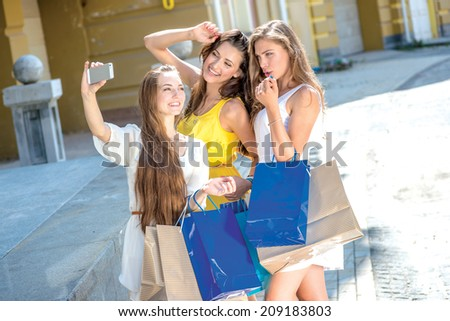Shopaholics do selfie on a cell phone. Girls holding shopping bags and walk around the shops. Smiling girl photographed on a cell phone. Girlfriends posing in front of the camera