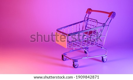 Shoping trolley with in trendy neon light. Gradient pink-blue glow. Concept art. Retro 80s. Minimalism shopping concept. Toy shopping trolley, neon