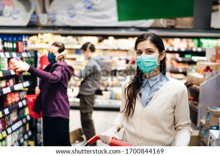 Shopper with mask safely buying for groceries due to coronavirus pandemic in grocery store.COVID-19 shopping.Quarantine preparation.Panic buying and stockpiling.Lockdown.Safety measures in supermarket